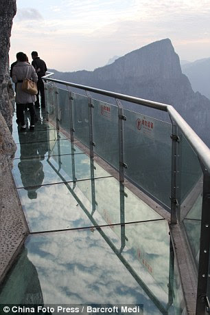 Tourists walk along the glass path that was built of the side of a cliff on Tianmen Mountain on November 9, 2011