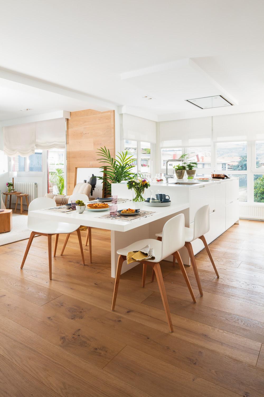 00452000. Cocina blanca comunicada con salón con mesa anexa y sillas también en blanco. Parquet 00452000