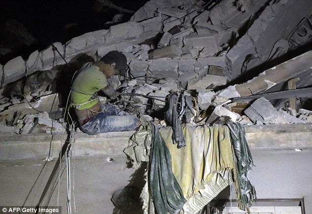 A young Syrian boy trapped in rubble waits to be rescued from a building following an airstrike in Aleppo