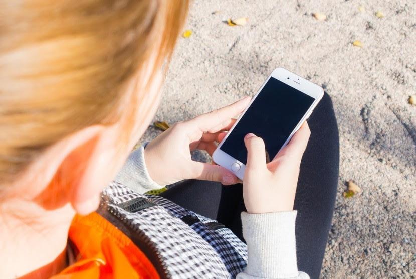 Remaja mengakses media sosial lewat gawainya.