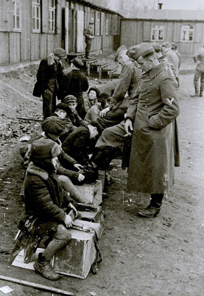 Русские дети чистят сапоги немецких солдат.  Ноябрь 1942 г. Белосток.