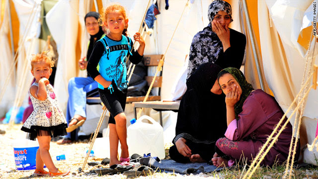 Syrian refugees sit in front of their tents Saturday in the southern part of Turkey.