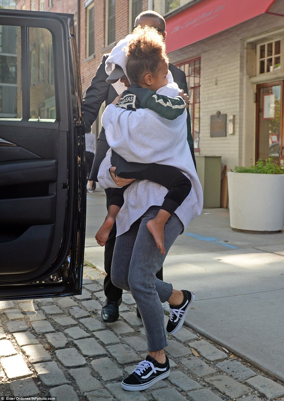 Protective: Kim kept her arms wrapped around her three-year old daughter as a driver held their car door open