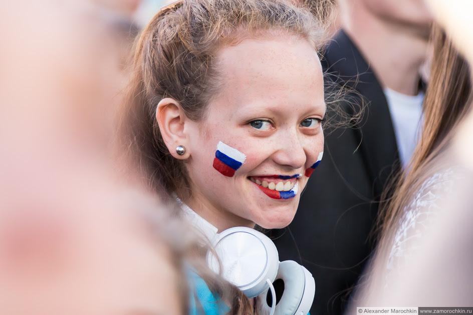 Девушка с российским флагами нарисованными на лице на фестивале FIFA Fan Fest в Саранске
