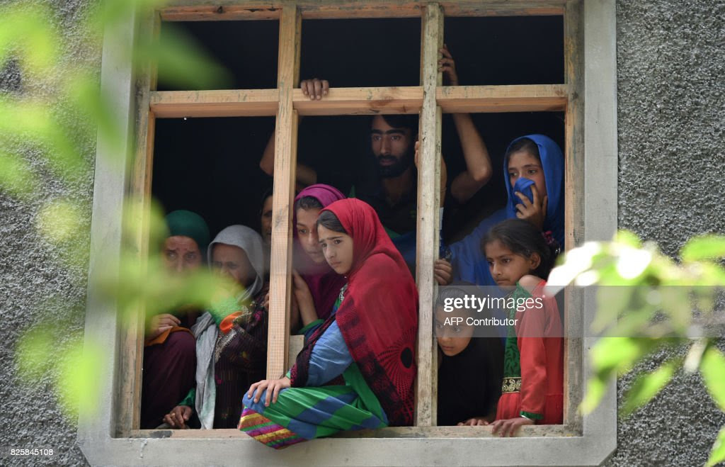 Kashmiri villagers watch the funeral procession of suspected rebel Suhail Ahmed Rather in the village of Tantraypora in Kulgam on August 3, 2017. Two suspected militants were killed August 3 in an encounter with security forces in Kulgam district of south Kashmir, police said. / AFP PHOTO / Tauseef MUSTAFA