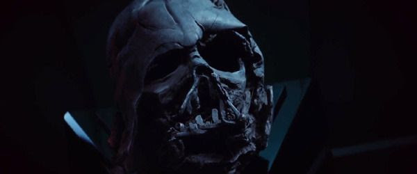 A mysterious individual stares at the charred remains of Darth Vader's helmet in STAR WARS: THE FORCE AWAKENS.