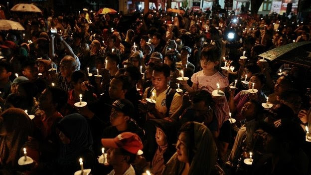 Indonesians light candles during a prayer for victims of the AirAsia flight QZ8501 crash in Surabaya, Indonesia, 31 December 2014