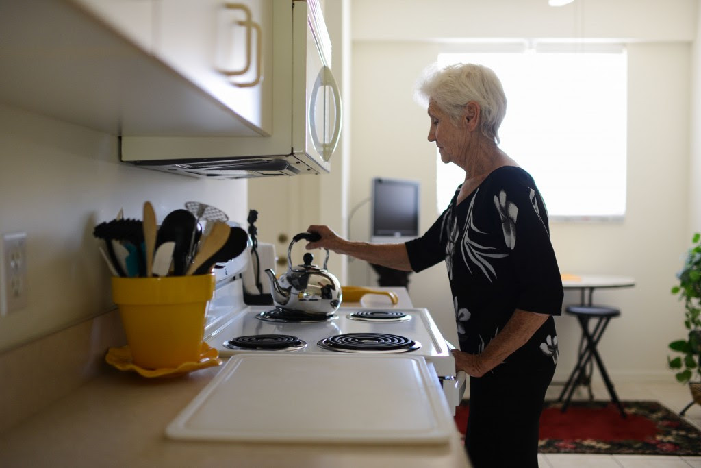 Dorothy Abruzzo boils water in her kitchen. Photo by Ariel Min/PBS NewsHour