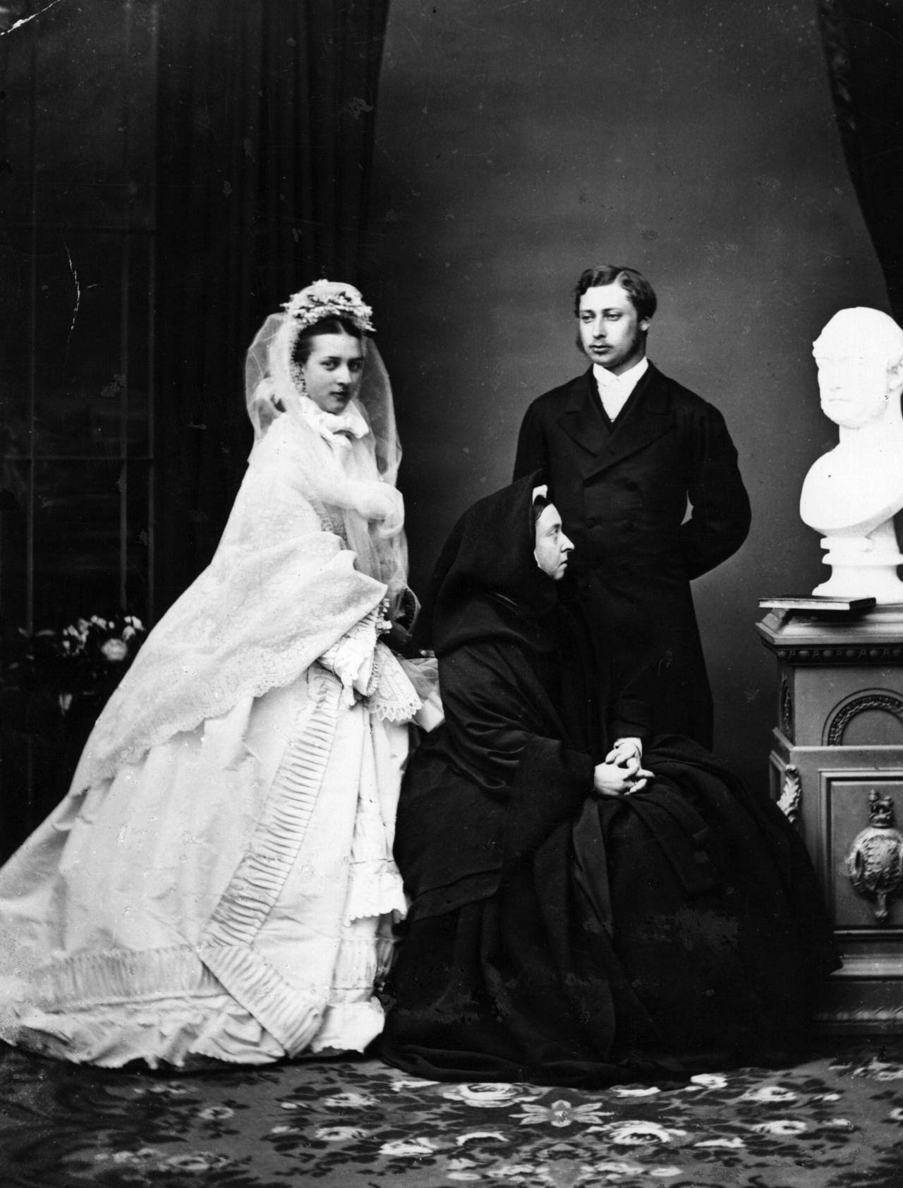 Queen Victoria insists on staring at a bust of her dead husband during her eldest son and heir's wedding photographs. 1863.