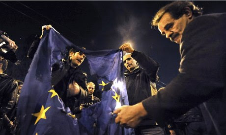 Greek demonstrators burn an EU flag