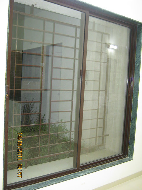 6 feet powder coated aluminium sliding window with a mosquito net & a safety grill in a marble frame in a 2 BHK Sample Flat in Om Developers' Tropica, Blessed Township at Ravet PCMC, Pune 412 101