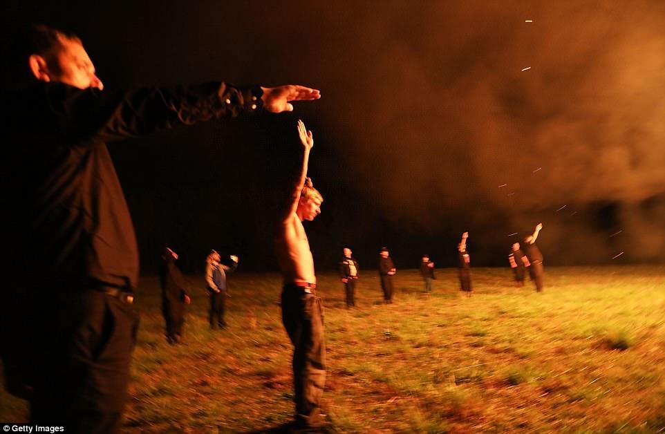 Un hombre sin camisa tiene las dos manos en la cabeza mientras otros sacan los saludos nazis mientras las llamas de la esvástica ardiente llenan el aire de la noche