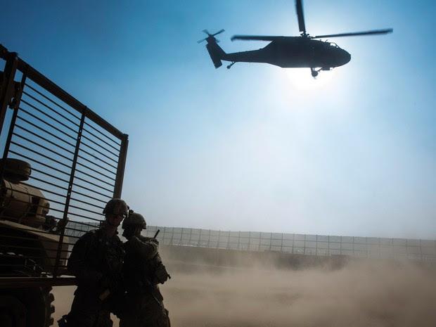 Soldados norte-americanos do 3º Regimento de Cavalaria cobrem seus rostos durante decolagem do helicóptero Blackhawk em missão para inspecionar uma instalação da Polícia Nacional Afegã na província de Nangarhar, no Afeganistão (Foto: Lucas Jackson/Reuters)