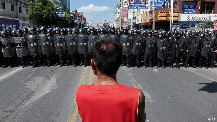 A protester stands in front of a lines of riot police officers Saturday July 28, 2012 in Qidong, Jiangsu Province, China. Authorities in eastern China dropped plans for a water-discharge project Saturday after thousands of protesters angry about pollution took to the streets, in the latest of many such confrontations in a country where three decades of rapid economic expansion have come at an environmental price. (Foto:Eugene Hoshiko/AP/dapd)