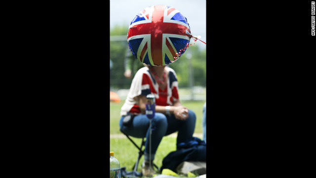 A Union Jack balloon floats in front of a woman wearing a Union Jack T-shirt as she waits for a giant picnic in Hyde Park.