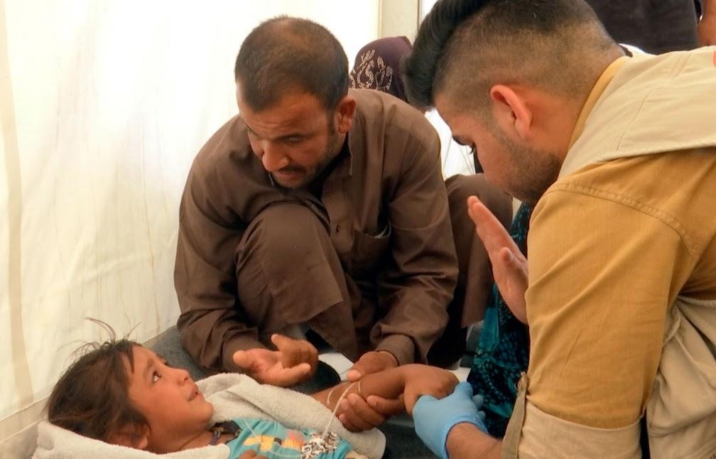 Menina é confortada pelo pai enquanto recebe atendimento médico no campo no campo de refugiados Hasansham U2, no norte do Iraque  (Foto: Balint Szlanko/ AP)