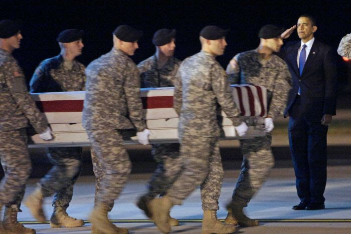 Six US soldiers carry a coffin past Barak Obama, who stands in salute.