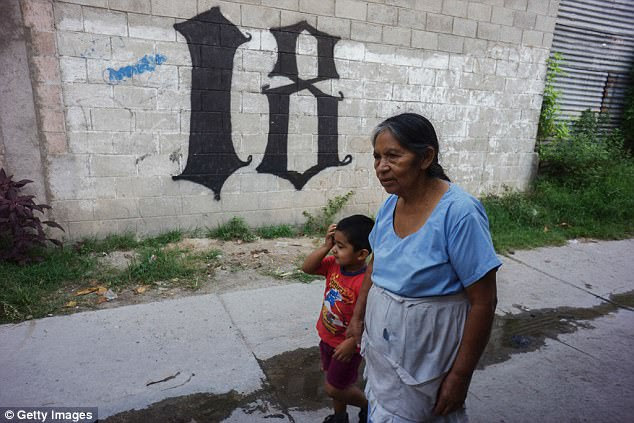 The gang has sown terror from its origin in Los Angeles throughout Central America. Pictured: A grandmother and her grandson walk past Barrio 18 graffiti in San Salvador