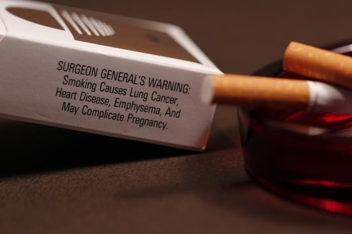 Ashtray with two cigarettes and cigarette box with Surgeon General's Warning: Smoking Causes Lung Cancer, Heart Disease, Emphysema, And May Complicate Pregnancy