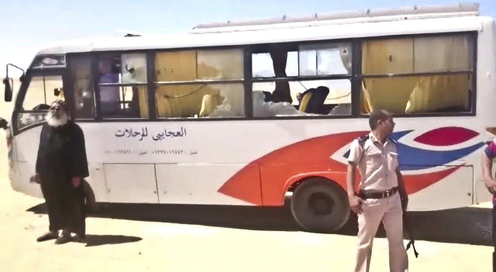 Policial e padre são vistos ao lado de ônibus que foi atacado nesta sexta-feira (26) no Cairo (Foto: Minya Governorate Media office via AP)
