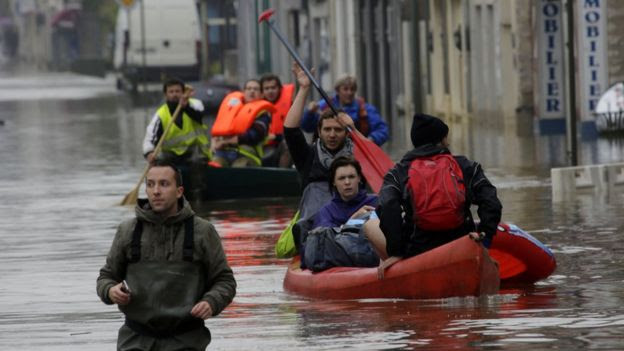 People in Nemours, France, paddle through flooded streets