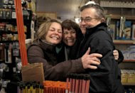 """In this photo taken Saturday, Jan. 21, 2012, shoppers and long time friends Cheryl Black, left, and Sherry Williams hug Jack Shutts at Chagrin Hardware in Chagrin Falls, Ohio. Black's husband Jim wrote an email to 40 friends asking them to pass the word along to """"Occupy CF Hardware"""" on Saturday and spend at least $20.00 in support of the owners, the Shutts family. (AP Photo/Amy Sancetta)"""