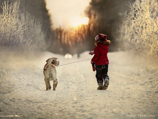 ภาพถ่ายหมาและเด็กเดินท่ามกลางหิมะ