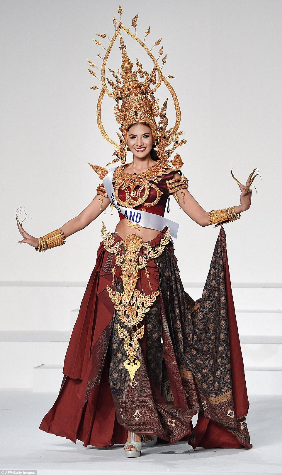 Miss Thailand wore the traditional dress of a fingernail dancer, which you would recognise if you have ever been to Thailand, or indeed a fancy Thai restaurant. Of course Sasi Sintawee wore a particularly intricate one, with a temple-inspired headdress which is so detailed and tall it wouldn't look out of place in a Thai miniature village. The gold continued around the collar, cuffs and waist, with her dress itself made in a sumptuous red silk with Oriental skirt folds and fabric design