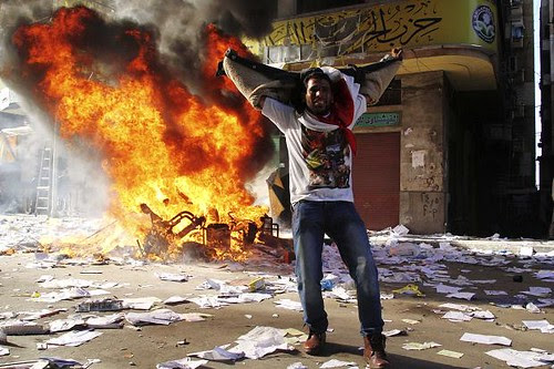 Man stands in front of Muslim Brotherhood allied Freedom and Justice Party (FJP) offices after they had been torched on November 23, 2012. Egypt has witnessed an upsurge in demonstrations. by Pan-African News Wire File Photos