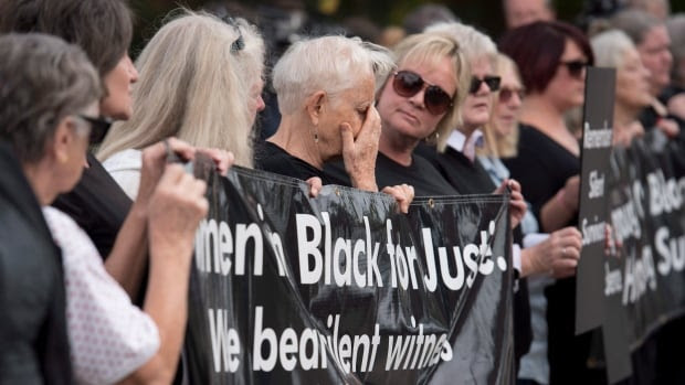 Women stand in solidarity in front of the courthouse in Pembroke, Ont., on Sept. 23, 2015, the day after the murders of three Renfrew County women.