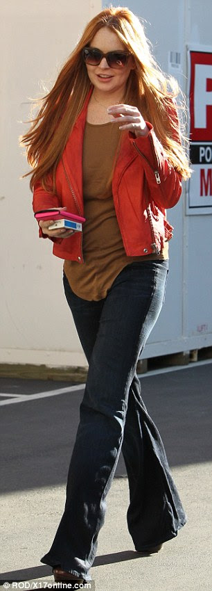 Red all around: To accentuate her signature hue today, Lindsay wore a bright red leather jacket paired with boot-leg cut jeans and an olive green top