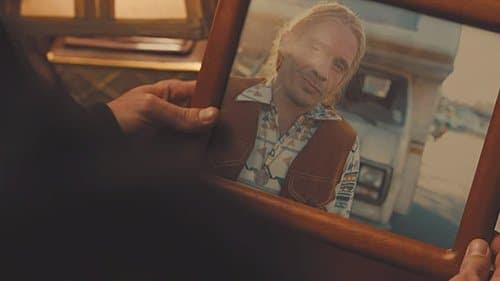 Detective Loki observa uma foto do marido de Holly usando um pingente labirinto.