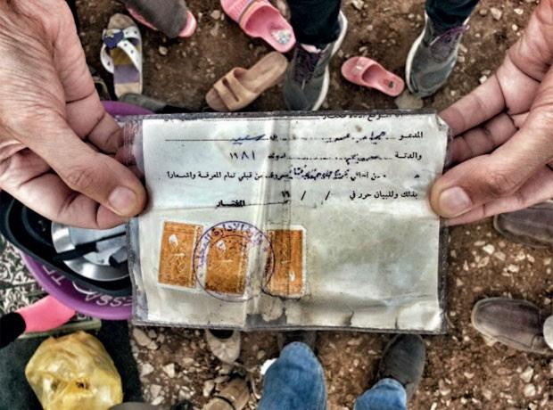 Refugiado sírio segura um cartão dado a curdos não-registrados, mas que não confere direito de nacionalidade (Foto: A.Sen/Acnur)