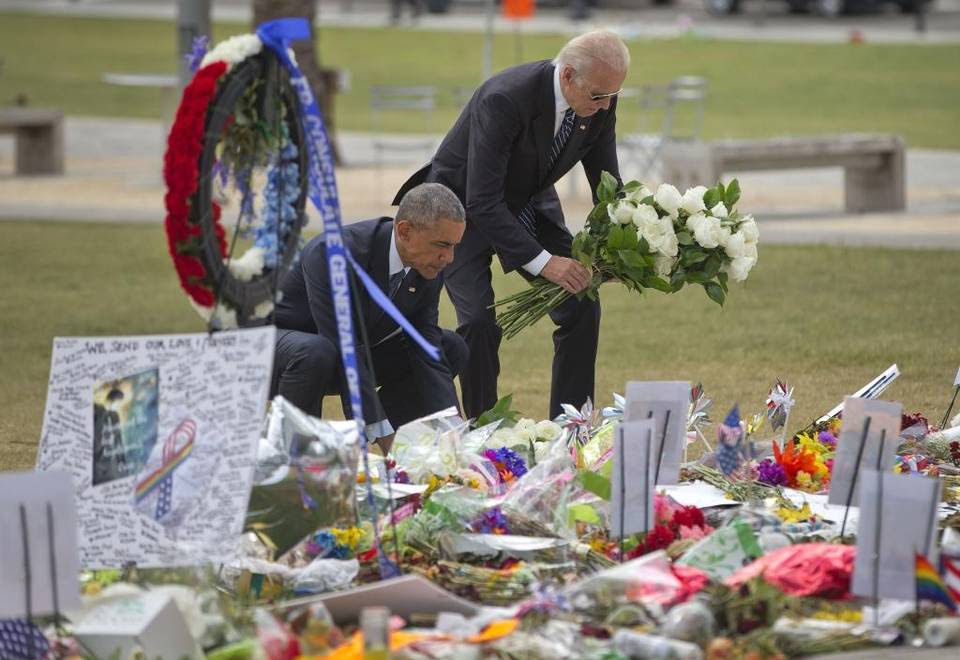 President Barack Obama and Vice President Joe Biden place flowers down during their visit to a memorial to the victims of the Pulse nightclub shooting, Thursday, June 16, 2016 in Orlando, Fla. Offering sympathy but no easy answers, Obama came to Orlando to try to console those mourning the deadliest shooting in modern U.S history.