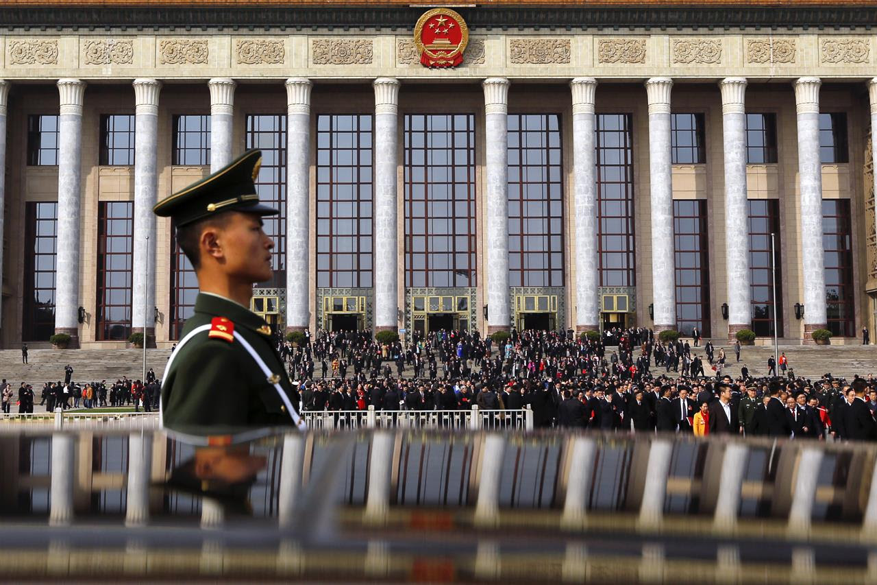 In this Wednesday, March 15, 2017 photo, a paramilitary policeman stands guard as delegates leave the Great Hall of the People after attending the closing session of the National People's Congress in Beijing, China.