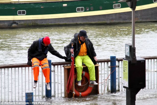 Members of the public were left stranded on railings after the Thames burst its banks and flooded streets alongside