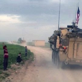 Syrian children watch as U.S. forces patrol a rural road in the village of Darbasiyah, in northern Syria. U.S. armored vehicles are deploying in areas in northern Syria along the tense border with Turkey, a few days after a Turkish airstrike that killed 20 U.S.-backed Kurdish rebels, April 28, 2017. (AP/APTV)