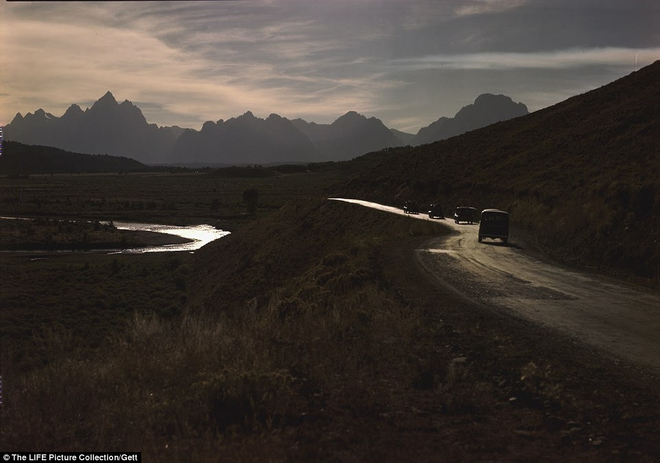 The route to Jackson Hole from the east: Cars pictured on Blackrock Creek with the Grand Tetons in the background