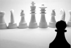 Ao fundo peças brancas de jogo de xadrez, em primeiro plano, um peão preto.