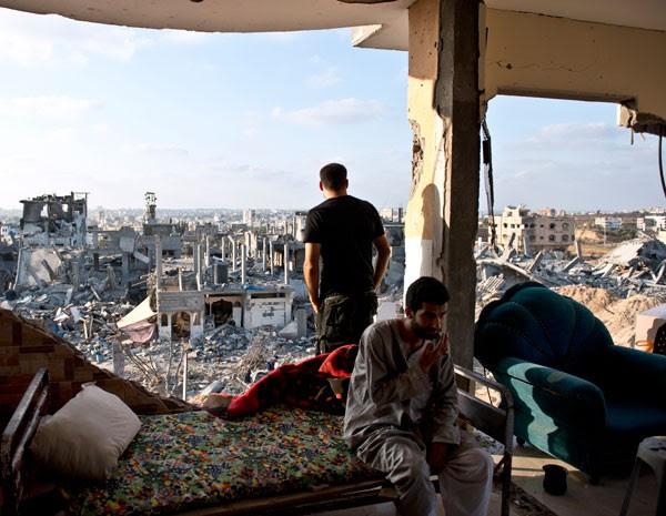 Palestinos sentam em apartamento destruído que viviam com suas famílias na faixa de Gaza. (Foto: ROBERTO SCHMIDT/AFP PHOTO)
