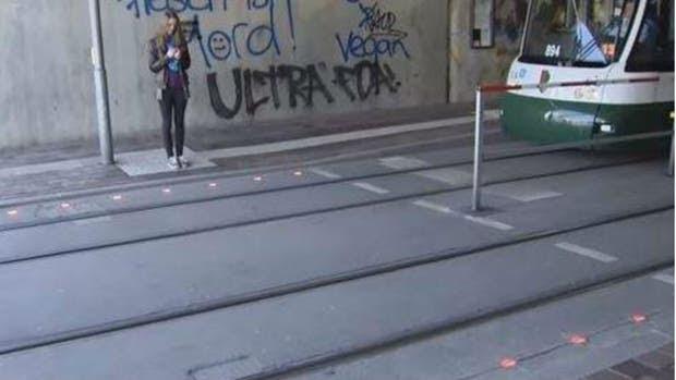 Luces rojas en el piso para peatones con celulares