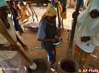 Locals pound grains outside their house in Maradi, Niger