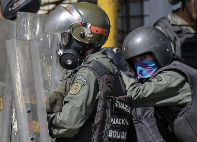 Un agente de la Guardia Nacional Bolivariana se protege detrás de su escudo