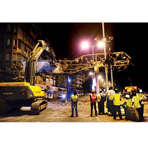 Civic officials oversee the demolition of the foot overbridge at Girgaum Chowpatty on Sunday.