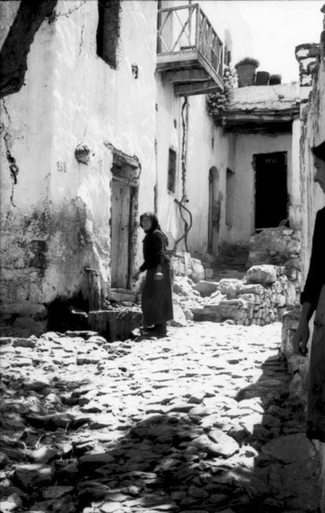 Γερμανοί αξιωματικοί προχωρούν με προσοχή μέσα στα στενά σοκάκια του χωριού, ενώ οι κάτοικοι τους κοιτούν μάλλον με περιέργεια.