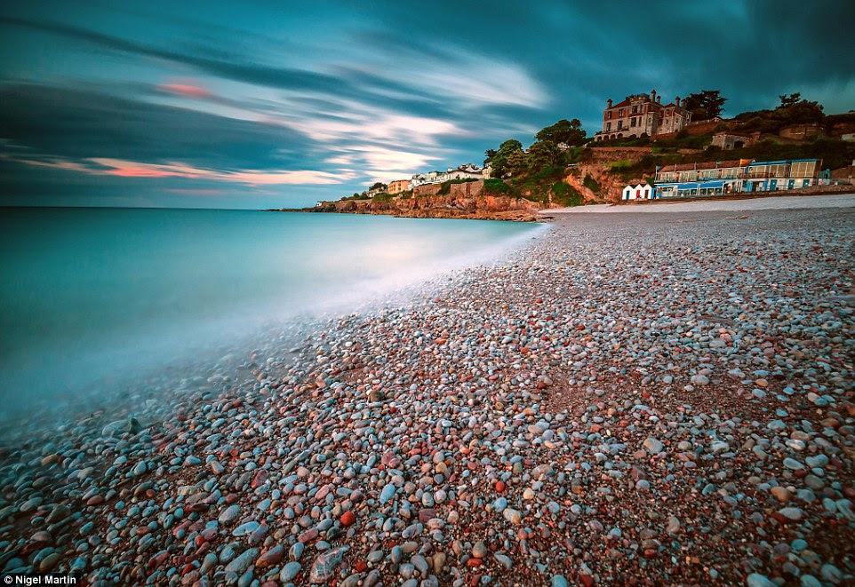 Os seixos sobre esta praia Devon parecem mostrar uma miríade de cores sob um céu nublado no quadro de Nigel Martin de uma tempestade em Brixham