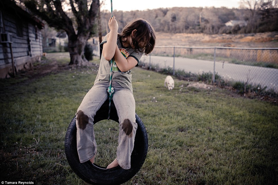 Simple pleasures: A young girl on a tire swing outside her home along Highway 70 in East Tennessee