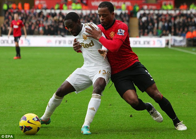 Protecting the ball: Nathan Dyer fends off the challenge of Evra