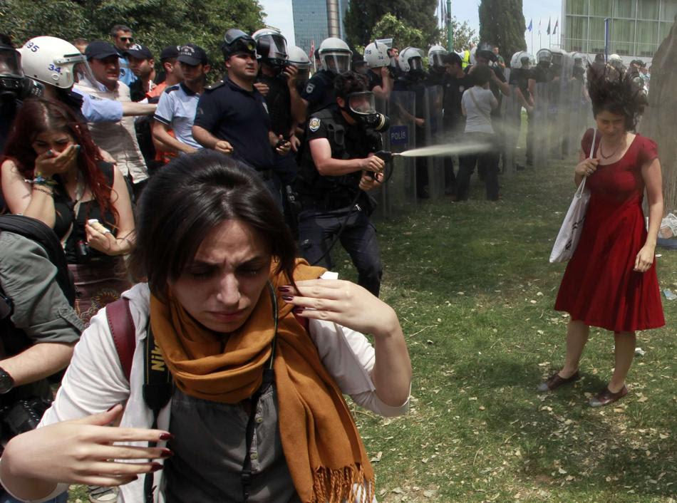 Άντρας των τουρκικών ΜΑΤ ρίχνει σπρέι πιπεριού σε μια γυναίκας που συμμετέχει σε μια διαμαρτυρία ενάντια στην καταστροφή των δέντρων που προκαλεί η κατασκευή μιας διάβασης πεζών στην πλατεία Ταξίμ στην Κωνσταντινούπολη  (28 Μαΐου του 2013. REUTERS / Osman Orsal)