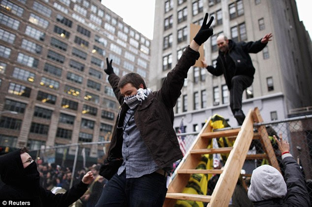 Occupy 2.0: Protesters descend a wooden ladder into a private area of Duarte Park in West SoHo to what they hope is a new encampment